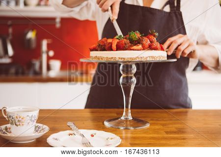 Unrecognizable confectioner cutting piece of cake on cake stand. Tea and plate on table.