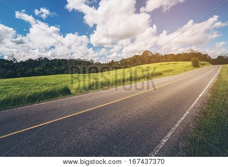 Road along hillside green grass under blue sky. Rural road. Up hill road. Vintage tone road.