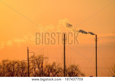 Smoke From The Boiler Pipes At Sunset. Winter Landscape