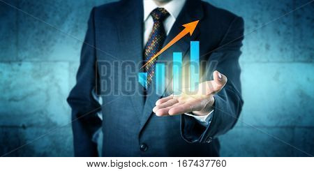 Manager in blue business suit is offering a virtual growth chart with upward soaring trend arrow in the upward facing open palm of his left hand. Business concept with positive outlook on future.