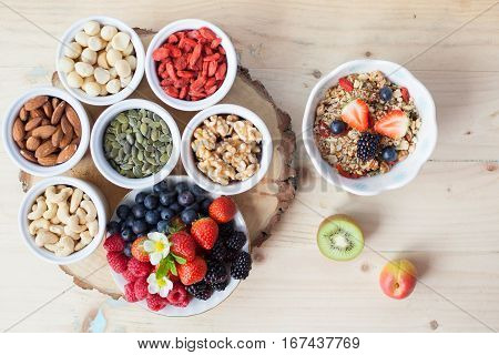 Paleo style breakfast: gluten free grain free oat free granola with mixed nuts and fresh berries and fruits selective focus; top view