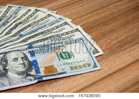 one hundred dollar bills on wooden table