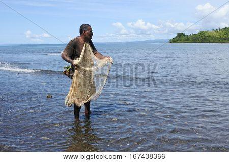 Indigenous Fijian Fisherman Fishing With A  Fishing Net In Fiji