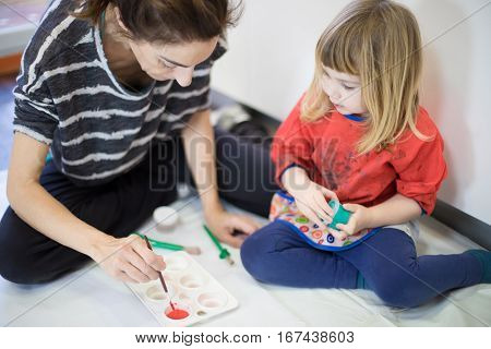 Woman And Child Preparing Red Paint