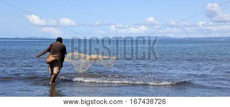 Indigenous Fijian Fisherman Throwing Fishing Net In Fiji