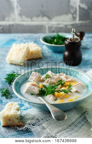 Homemade soup with chicken meat corn potatoes and parsley leaves in ceramic bowl. Simple stew. Selective focus.