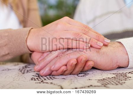Close up picture of elderly man holding his granddaughter's hands