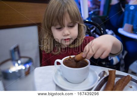 Happy Child Dipping Churros In Chocolate