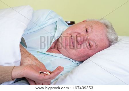 Picture of a bedridden elderly patient receiving his pills