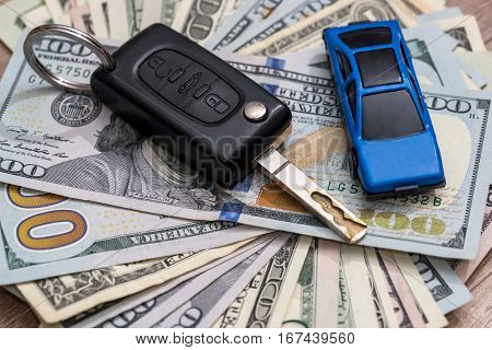 car key with pen and us dollar
