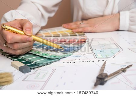 hands of designer woman working with color palette house design project at office desk