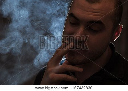 Young desperate caucasian man with cigarette in hands. Smoky background. Bad habits concept.