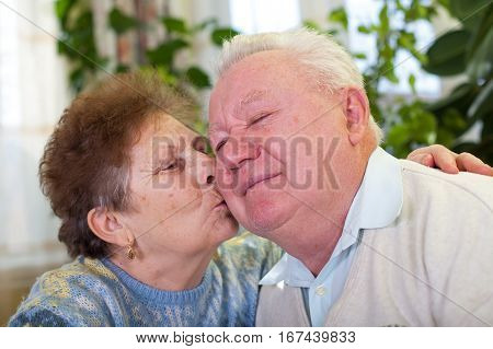 Picture of a cute elderly couple kissing at home