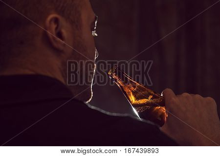 Cropped shot of young depressed man with beer bottle. Alcohol addiction. Bad habits concept.