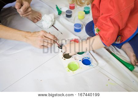 Woman And Child Team Working Preparing Paintings