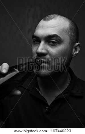 Portrait of young drunk man with beer bottle in hands. Alcohol addiction. Bad habits concept. Black and white image