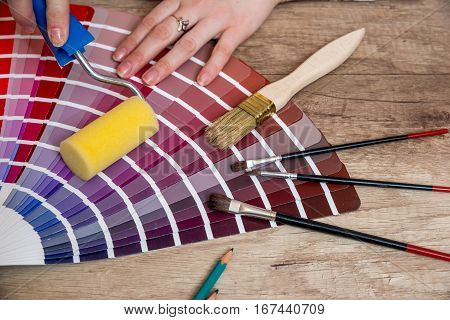 Woman hand showing to sample color chart with tools on desk
