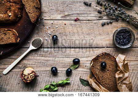 grapes wheat bread in wood table. dried roses. flowers. fruits grains food