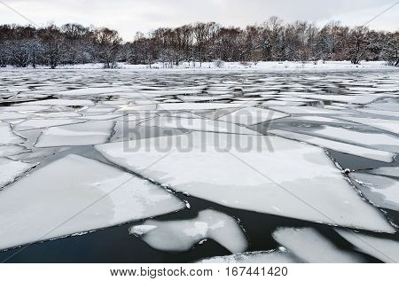 spring season - floating of ice on surface of river in twilight