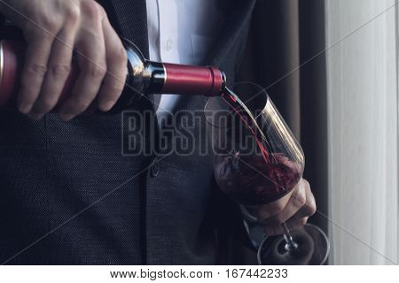 Horizontal close up of Caucasian man in black suit and white shirt pouring red wine into a tall glass in a bar