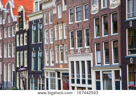 AMSTERDAM - JULY 10: Amsterdam city on July 10, 2016 in Amsterdam, Netherlands. The historical canals of the city surrounded by traditional dutch houses is one of the main attractions of Amsterdam.