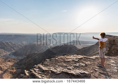 Rear View Of Tourist Looking At Expansive View Over The Fish River Canyon, Scenic Travel Destination
