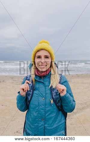 young woman hiker walking along the beach in winter. woman in a blue jacket and yellow knitted cap walking on the beach on the background stormy sea