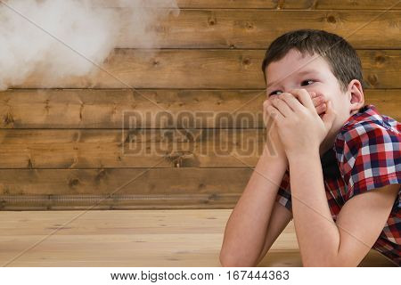 child covers his face from the smoke of cigarette against the wall for the label