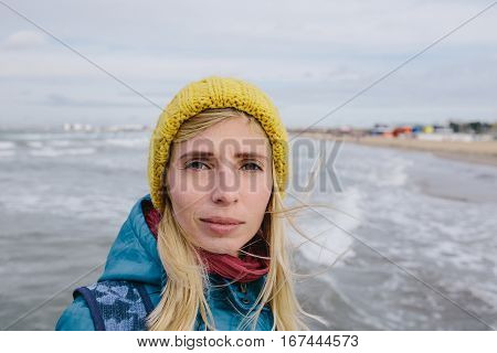 portrait of smiling young woman in a blue jacket and yellow knitted cap on the background stormy sea