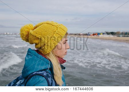 portrait of young woman in a blue jacket and yellow knitted cap on the background stormy sea