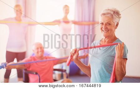 Portrait of seniors exercising with stretching bands during sports class