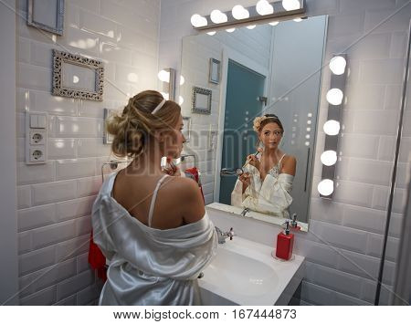 Young woman applying makeup in bathroom by makeup brush.