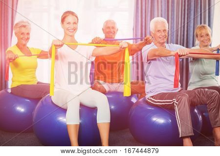 Portrait of seniors using exercise ball and stretching bands during sports class