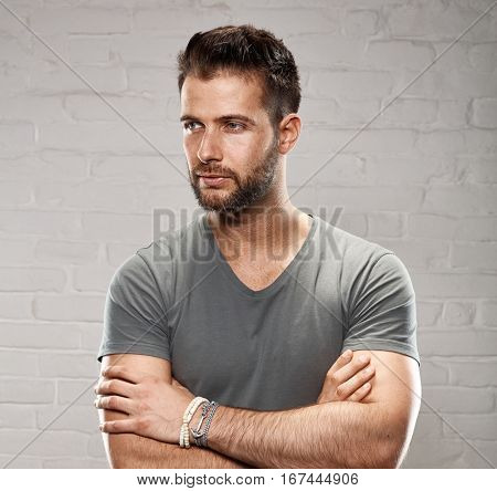 Portrait of young goodlooking man in casual clothing against white brickwall.