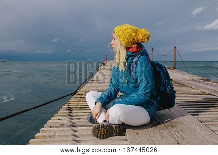 young woman sitting on a wooden pier and looking at stormy sea