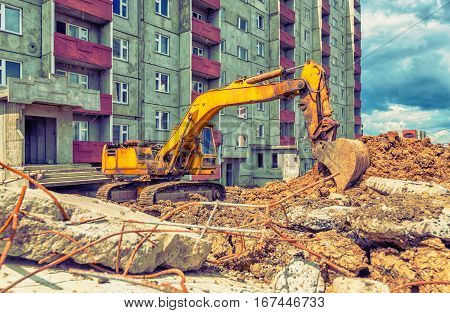 Yellow excavator in work on the construction site