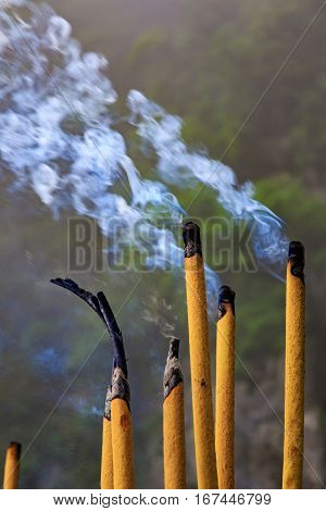 Photo of Smoke Sticks Burning Out with Silky Smoke. Asian Religion Aroma Sticks for Praying