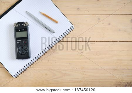 Digital sound recorder and other accessories on the wooden table, top view