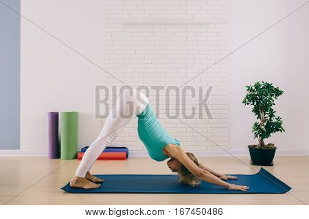 Step of surya namaskar downward facing dog pose by beautiful woman indoor