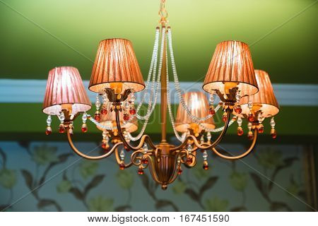 Chandelier ceiling, lights are on. Beautiful bronze chandelier with light bottles. CHANDELIER ON THE CEILING. chandelier on a chain with white bottles.