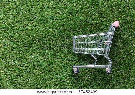 Self-service Supermarket Shopping Trolley Cart On Spring Or Summer Green Grass Lawn Background