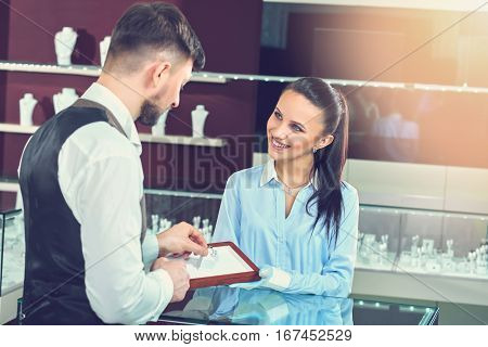 Rear view of brunet man choosing and buying jewelry for girlfriend. Jeweler in gloves showing engagement ring with blue stone. Looking, smiling each other and talking. Jewelry luxury store.