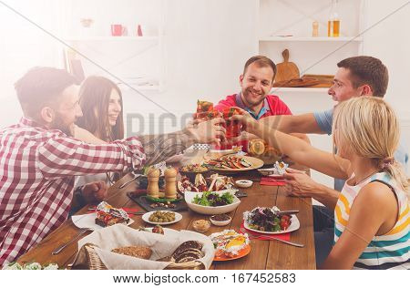 Group of people clink glasses, saying cheers, eat healthy meals at party dinner table in cafe, restaurant or at home. Young cute friends company celebrate with organic food at wooden table indoors.