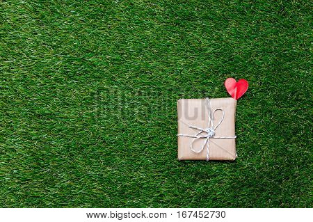 Red Little Gift Box On Spring Green Grass Lawn Background