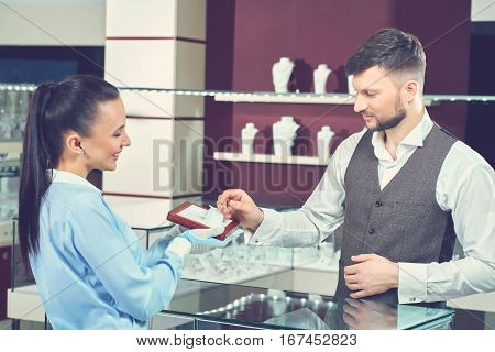 Female seller in jewelry store showing engagement ring for buyer. Young brunet man with beard choosing present for his girlfriend, touching for golden ring with blue stone and want buying it.