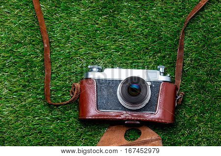 Vntage Camera In Case On Spring Green Grass Background