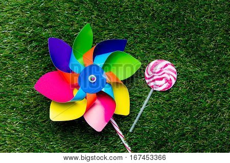 Pinwheel Toy And Lollipop Candy On Green Grass Background,