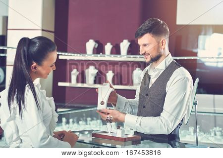 Side view of woman in blue blouse choosing necklace of gold jewelry set with brown shiny stones. Jeweler male brunet wearing shirt and vest of suite, showing for female buyer jewelry and smiling.