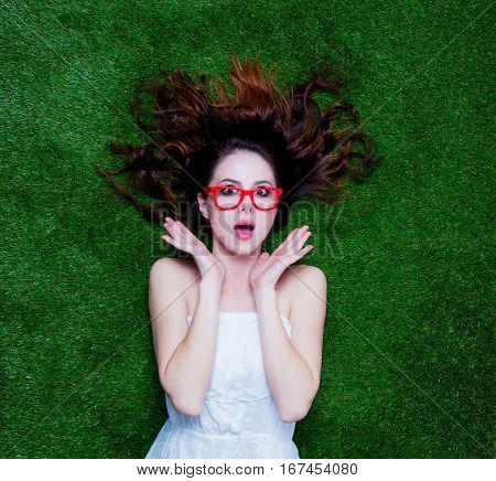 Portrait Of A Young Redhead Woman With Styled Glasses Lying Down On Green Spring Grass