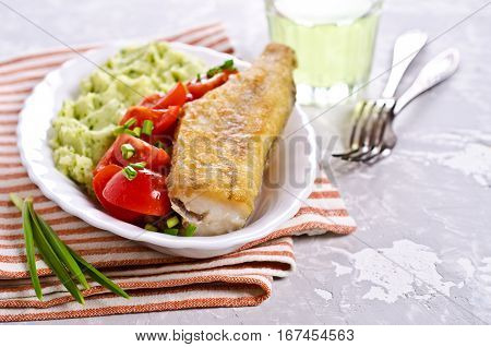 Fried pollock with vegetables on a plate. Selective focus.